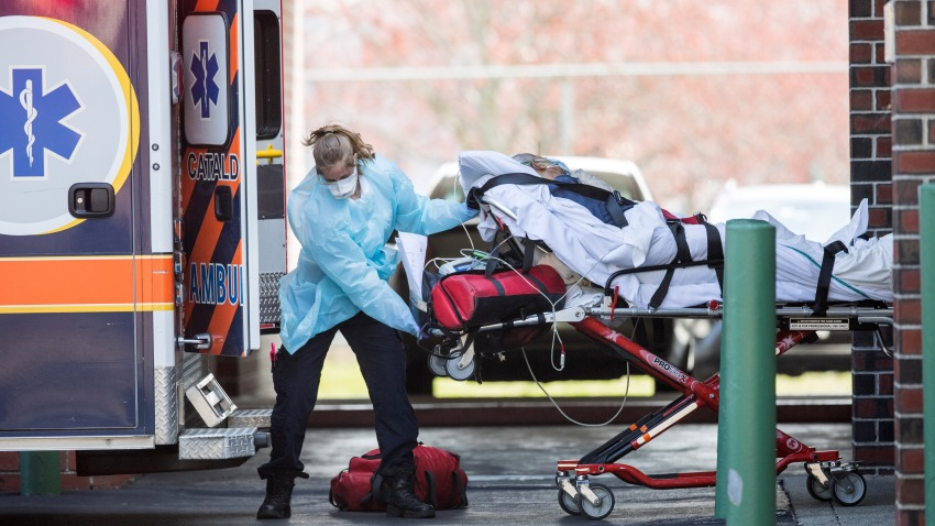 In this April 17, 2020, file photo, a first responder wheels a COVID-19 patient into an ambulance in Chelsea, Massachusetts.