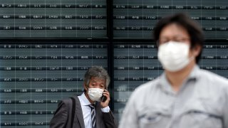 A man stands in front of a blank electronic stock board supposedly showing Japan's Nikkei 225 index at a securities firm in Tokyo Thursday, Oct. 1, 2020. Trading on the Tokyo Stock Exchange was suspended Thursday because of a problem in the system for relaying market information. Most other Asian markets were closed for national holidays.