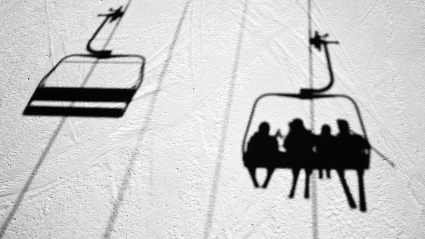 People on a Vermont ski lift are seen in silhouette in the snow
