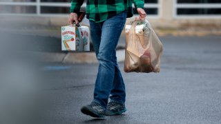 A man carry his groceries out of a Maine Hannaford in a plastic bag.
