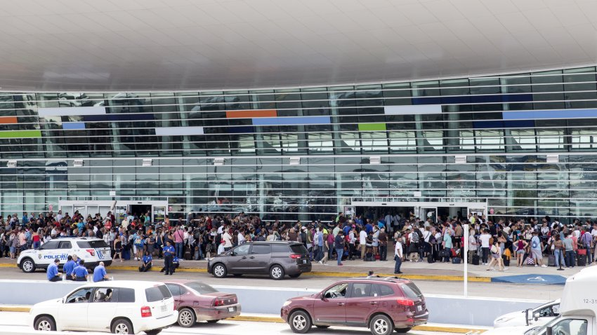 Travelers stand in line outside of Luis Muoz Marn International Airport after Hurricane Maria disrupted flight service in San Juan, Puerto Rico on Wednesday, Sept. 27, 2017. PresidentDonald Trumpsaid he may temporarily suspend a law that restricts the use of foreign ships operating in U.S. waters and between U.S. ports in order to accelerate the delivery of aid to Puerto Rico, where his administration faces mounting criticism over its response to Hurricane Maria.