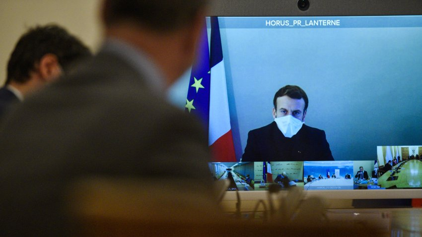 French President Emmanuel Macron is seen on a screen from his presidential residence in Versailles as he attends by video conference the weekly cabinet meeting at the Elysee Palace in Paris, Monday, Dec. 21, 2020.