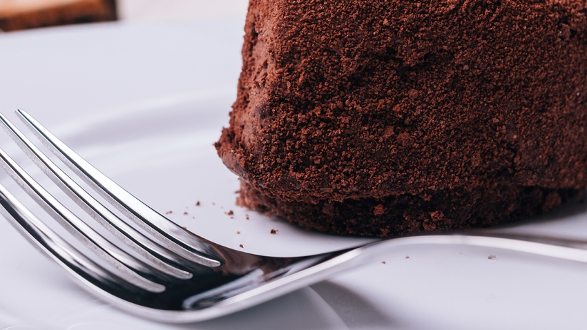 Close up of chocolate cake and fork in the foreground