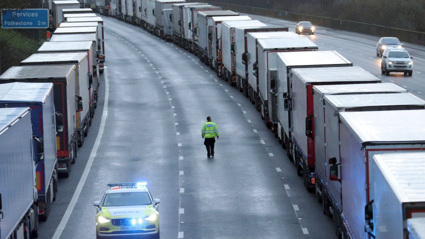 Police patrol along the M20 motorway where freight traffic is parked whilst the Port of Dover remains closed, in Ashford, Kent, England, Tuesday, Dec. 22, 2020. Trucks waiting to get out of Britain backed up for miles and people were left stranded at airports as dozens of countries around the world slapped tough travel restrictions on the U.K. because of a new and seemingly more contagious strain of the coronavirus in England.