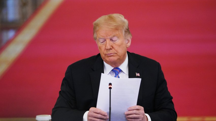 US President Donald Trump holds papers during an American Workforce Policy Advisory Board Meeting in the East Room of the White House in Washington, DC on June 26, 2020