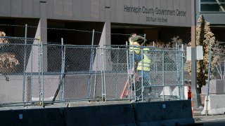 Workers install barbed wire on fencing outside the Hennepin County Government Center