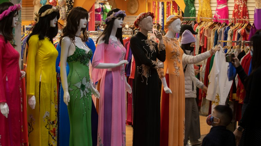"Westminster, CA - February 10: Shoppers view mannequins dressed in the áo dài, the traditional Vietnamese dress outfit, at the Asian Garden Mall in preparation for the Lunar New Year in Little Saigon, Westminster Wednesday, Feb. 10, 2021. For those who celebrate Lunar New Year, which starts Friday, Feb. 12, COVID has forced them to avoid touching cash and stuff traditional red envelopes normally filled with ""lucky"" money instead with checks, Lotto tickets, gift cards and the like. It will be the Year of the Ox. People flocked to Little Saigon to purchase holiday wares, traditional Vietnamese outfits, baked goods or flowers set up at store entrances or along the sidewalk."