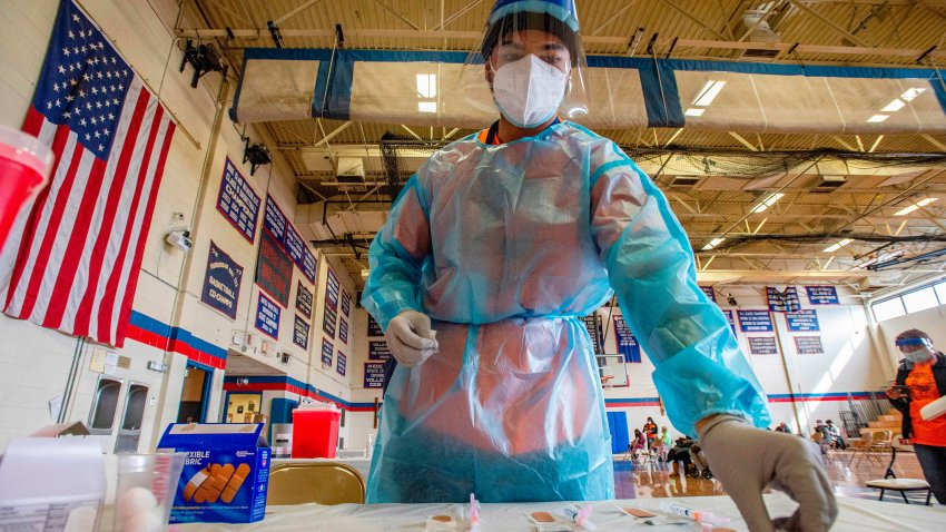 Elvin Toro, 26, a former army medic, organizes his syringes before giving out the next doses to a local resident at Central Falls High School in Central Falls, Rhode Island