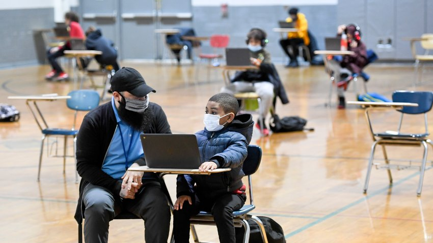 In this Jan. 19, 2021, file photo, Jordan Rodriguez, director of the Mulberry Street location of the Olivet Boys and Girls Club in Reading, works with Santana Sanford, a second grade student, as he does his school work on a laptop computer.