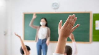 students in class raise hands