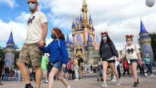 A masked family walks past Cinderella Castle in the Magic Kingdom in DisneyWorld