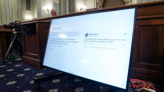 Tweets from President Donald Trump are displayed on a screen