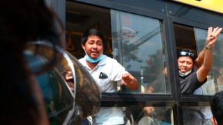 An arrested protester flashes the three-fingered salute while onboard a bus getting out of Insein prison to go to an undisclosed location Wednesday, March 24, 2021 in Yangon, Myanmar.