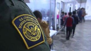 agente de la patrulla fronteriza vigilando a menores en centro de procesamiento