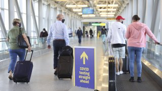 In this March 26, 2021, file photo, travelers wearing protective masks walk past a sign pointing towards a Covid-19 testing location in Terminal 5 at John F. Kennedy International Airport (JFK) in New York.