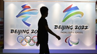 In this 2018 file photo, a visitor walks past logos of the upcoming Beijing 2022 Winter Olympic and Paralympic Games during the Beijing Olympic Expo marking the 10th anniversary of the 2008 Olympic Games, in Beijing.