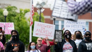 Demonstrators hold signs during a protest march in Elizabeth City, North Carolina