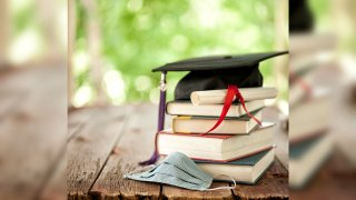 A graduation cap and diploma on a stack of books next to a face mask