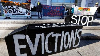 FILE - In this Jan. 13, 2021, file photo, demonstrators hold signs in front of the Edward W. Brooke Courthouse in Boston. A federal judge has ruled, Wednesday, May 5, 2021, that the Centers for Disease Control exceeded its authority when it imposed a federal eviction moratorium to provide protection for renters out of concern that having families lose their homes and move into shelters or share crowded conditions with relatives or friends during the pandemic would further spread the highly contagious virus.