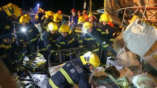 Emergency personnel search through the wreckage of buildings destroyed by a reported tornado in Wuhan in central China's Hubei Province