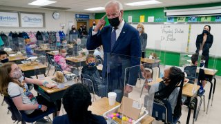 In this May 3, 2021, photo, President Joe Biden gestures as he talks to students during a visit to Yorktown Elementary School, in Yorktown, Va., as first lady Jill Biden watches. Biden has met his goal of having most elementary and middle schools open for full, in-person learning in his first 100 days.