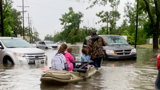 Parents use boats to pick up students from schools after nearly a foot of rain fell in Lake Charles, La., on May 17.