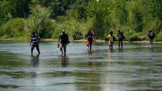 A group of migrants walk across the Rio Grande river.