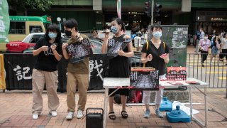 Chow Hang Tung, vice chairperson of the Hong Kong Alliance in Support of Patriotic Democratic Movements of China, left, and other activists at a sidewalk booth showcasing the 1989 Tiananmen Square crackdown in Hong Kong, on Saturday, May 29, 2021.