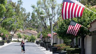 A man walks along a street where U.S. flags fly.