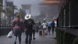 Pedestrians walk past misters along the Strip in Las Vegas, Nevada, U.S., on Wednesday, June 16, 2021. The searing weather marks the first heat-related stress tests of the year for U.S. power grids as a historic drought grips the western half of the nation.
