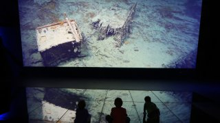 BELFAST, NORTHERN IRELAND - MARCH 27: Visitors look at a projection showing images of the wreck of the Titanic on the seabed at the Titanic Belfast visitor attraction on March 27, 2012 in Belfast, Northern Ireland. The Titanic Belfast Experience is a new £90 million visitor attraction opening on March 31, 2012. One hundred years ago the maiden voyage of the ill-fated passenger liner Titanic sank after hitting an iceberg in the Atlantic on the night of April 14, 1911 with the loss of 1517 lives.