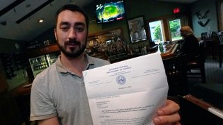 David Culhane, owner of the White Mountain Tavern, holds up a November 2020 letter from the N.H. Attorney General's office, notifying that his business was in violation, and also fined, after breaking an emergency order, July 13, 2021, in Lincoln, New Hampshire.
