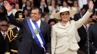 FILE - In this Jan. 27, 2010 file photo, wearing the presidential sash, Honduran President Porfirio Lobo and his wife First Lady Rosa Elena wave after Lobo was sworn in as the new president during his inauguration ceremony in Tegucigalpa. The U.S. State Department has named in a report released on Thursday, July 1, 2021 more than 50 current and former officials suspected of corruption or undermining democracy in three Central American countries, including the former Honduran first couple, saying Lobo took bribes from a drug cartel and his wife was involved in fraud and misappropriation of funds. Both deny the allegations.