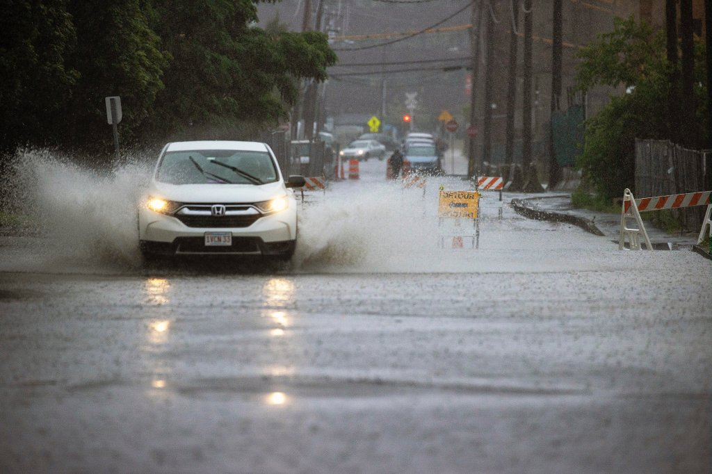 A car makes a huge splash driving on the flooded streets
