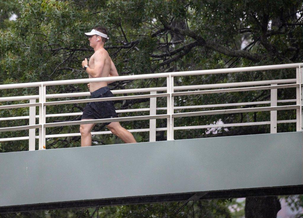 A man runs down a bridge during Tropical Storm Elsa