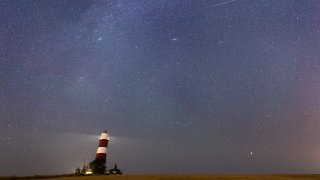 A meteor during the Perseid meteor shower seen over Happisburgh lighthouse, Norfolk, as the Earth flies through a cloud of cometary dust creating a spectacular display of celestial fireworks.