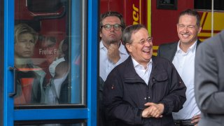 North Rhine-Westphalia's State Premier, Christian Democratic Union (CDU) leader and CDU's candidate for Chancellery Armin Laschet (C) laughs while the German President (unseen) delivers a speech after they visited the Rhein-Erft fire and rescue control center and in Erftstadt, western Germany, on July 17, 2021.