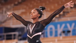 Simone Biles stands with her arms raised.