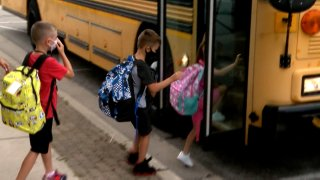 Children board a school bus