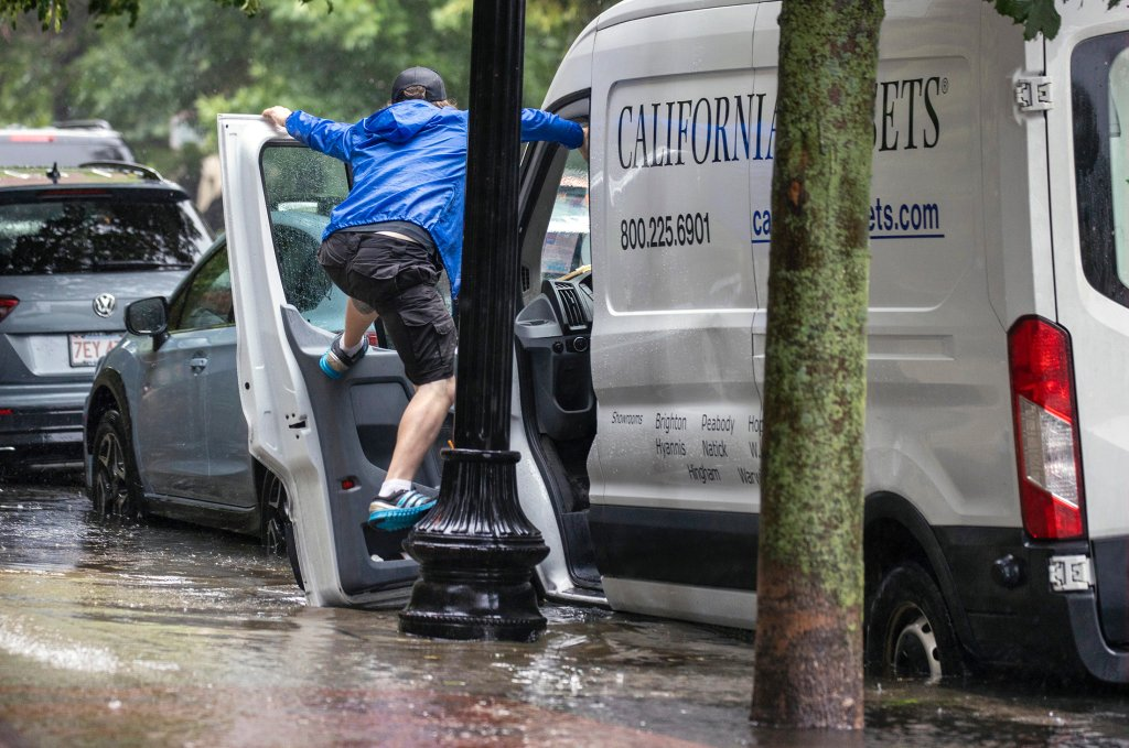 A man tries to avoid flood water by hanging onto his car door