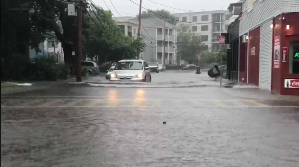 A car drives through deep water on a flooded Kendall Street in Framingham