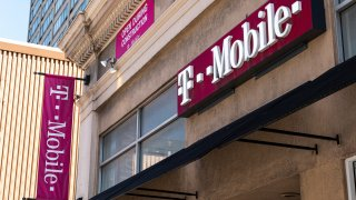 Signage for a T-Mobile store in San Francisco, California, U.S., on Tuesday, March 16, 2021. T-Mobile US Inc. is kicking off a bond sale to help finance the purchase of new high-speed spectrum licenses as carriers roll out the next generation of mobile devices.