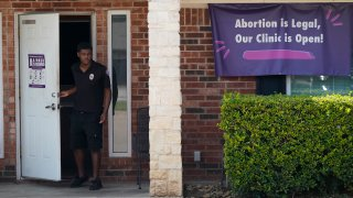 FILE - In this Sept. 1, 2021 file photo, a security guard opens the door to the Whole Women's Health Clinic in Fort Worth, Texas. Even before a strict abortion ban took effect in Texas this week, clinics in neighboring states were fielding more and more calls from women desperate for options. The Texas law, allowed to stand in a decision Thursday, Sept. 2, 2021 by the U.S. Supreme Court, bans abortions after a fetal heartbeat can be detected, typically around six weeks.
