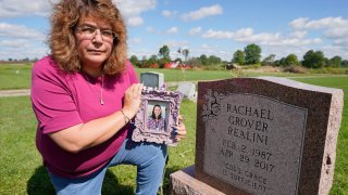 Sharon Grover holds a photograph of her daughter, Rachael, over the gravesite at Fairview Cemetery