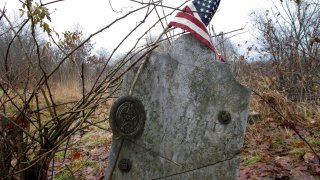This Dec. 10, 2019, photo shows the gravestone of Revolutionary War soldier William Haven who is buried in a cemetery in Weybridge, Vt., near the edge of an eroding river bank. Rising seas, erosion and flooding from worsening storms that some scientists believe are caused by climate change are putting some older graveyards across the country at risk.