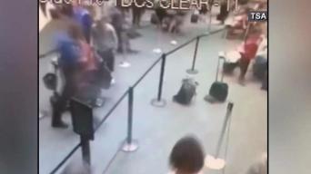 TSA Agent Grabs Smoking Bag Before it Explodes