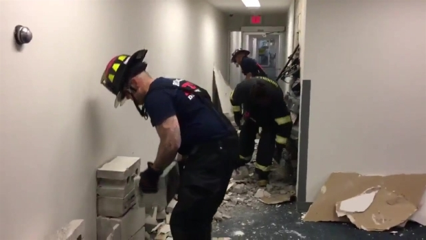[NECN] Fire Crews Work to Remove BMW Stuck in Condo Building Wall