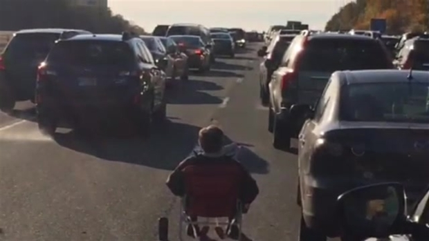 Man Sits in Chair on Highway, Reads Newspaper
