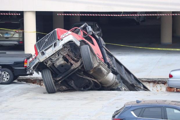 UP CLOSE: Dump Truck Crashes Through Quincy Parking Garage Roof