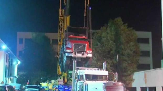 [NECN] Dump Truck Removed From Quincy Garage After Falling Through Structure